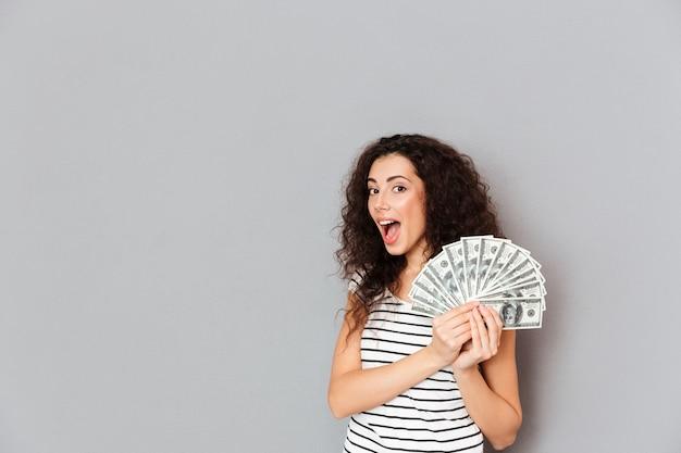 Mulher linda em camiseta listrada, segurando o leque de notas de 100 dólares nas mãos, sorrindo para a câmera, sendo feliz e sortudo sobre parede cinza Foto gratuita