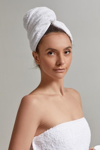 Mulher linda morena usando toalha branca depois do banheiro Foto Premium