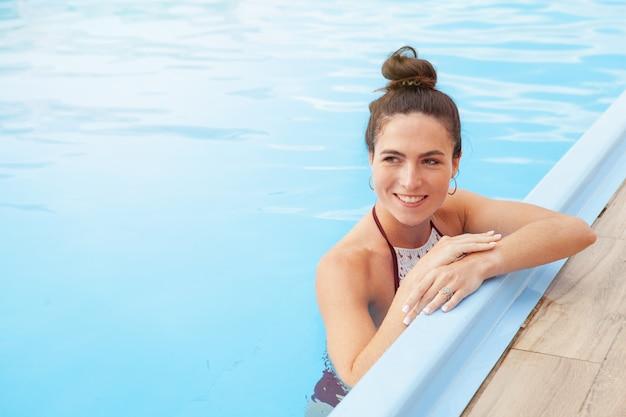 Mulher linda relaxante na piscina Foto Premium