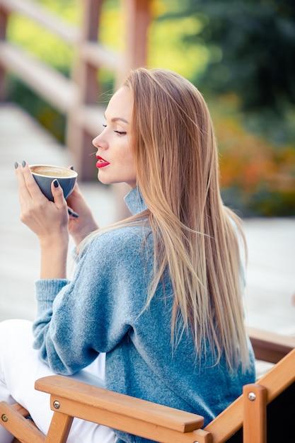 Mulher linda tomando café no parque outono sob folhagem de outono Foto Premium