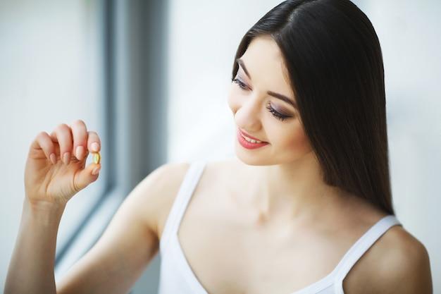 Mulher linda tomando pílula, medicina. vitaminas e suplementos Foto Premium