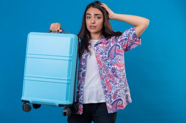 Mulher linda turista em pé com uma mala de viagem, parecendo confusa com a mão na cabeça por engano, lembre-se do erro, esqueci o conceito de memória ruim sobre o espaço azul isolado Foto gratuita