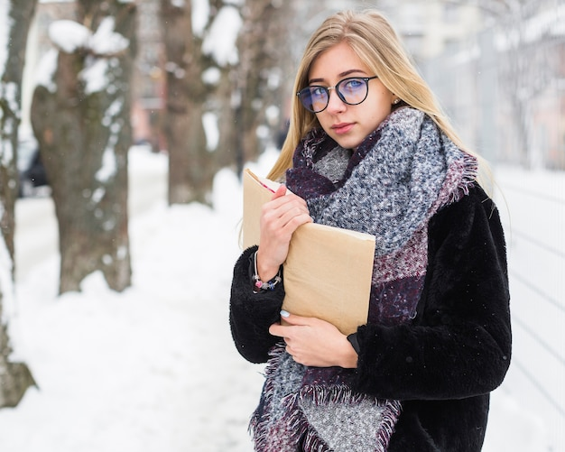 Mulher, livro, olhar, câmera, inverno, rua Foto gratuita