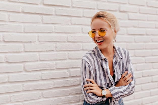 Mulher loira adorável feliz usando óculos laranja elegantes em uma camisa listrada e posando com um sorriso adorável Foto gratuita