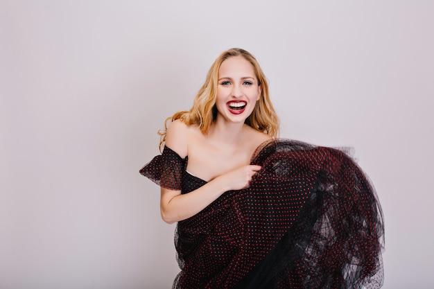 Mulher loira alegre dançando e segurando a saia nas mãos, se divertindo na festa, curtindo. usando vestido preto fofo, tem cabelos longos e cacheados. Foto gratuita