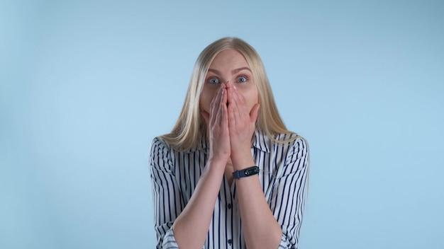 Mulher loira amplamente abrindo a boca em espanto Foto Premium
