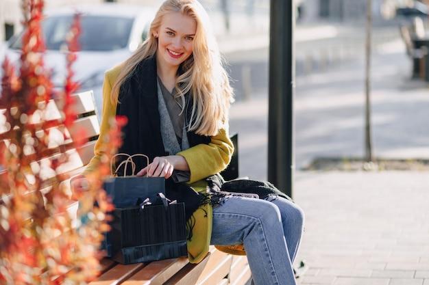 Mulher loira atraente bonita feliz com pacotes na rua em um clima quente e ensolarado Foto gratuita