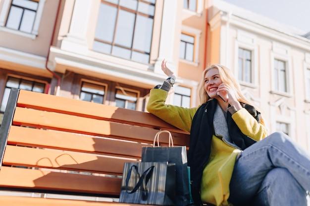 Mulher loira atraente feliz fofa com pacotes na rua em tempo ensolarado Foto gratuita