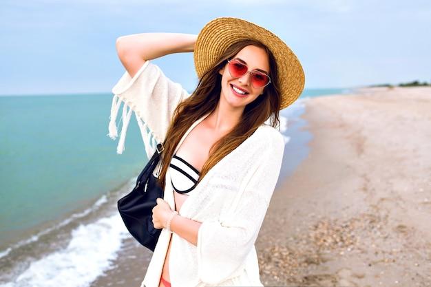 Mulher loira bonita fazendo selfie na praia do oceano, vestindo roupa de boho e óculos de sol engraçados, chapéu de palha vintage, mandando beijar você. Foto gratuita