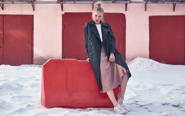 Mulher loira bonita hipster vestindo casaco longo da moda e vestido na rua Foto Premium