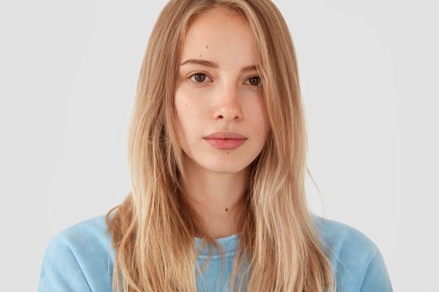 Mulher loira com camisa azul posando Foto gratuita