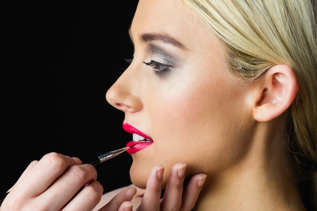 Mulher loira, com os lábios compostos pelo maquiador Foto Premium