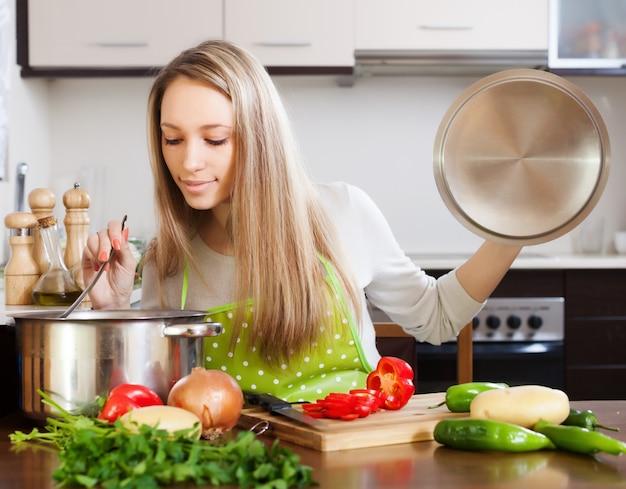 Mulher loira com sopa de sopa de panela da panela Foto gratuita
