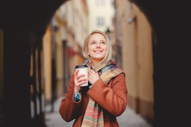 Mulher loira com uma xícara de café na cidade velha Foto Premium