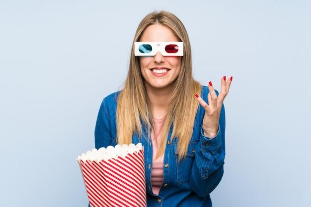 Mulher loira comendo pipocas irritado irritado em gesto furioso Foto Premium