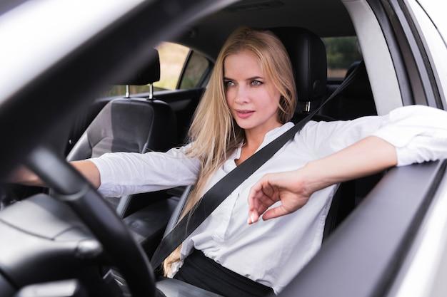 Mulher loira cuidadosa dirigindo um carro Foto gratuita