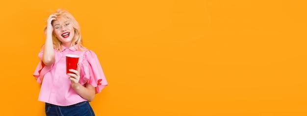 Mulher loira de blusa rosa com copo vermelho Foto Premium