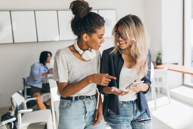 Mulher loira de jeans e óculos segurando o smartphone enquanto falava com o amigo africano no escritório. aluna muito internacional em fones de ouvido, passando um tempo com colegas de universidade. Foto gratuita