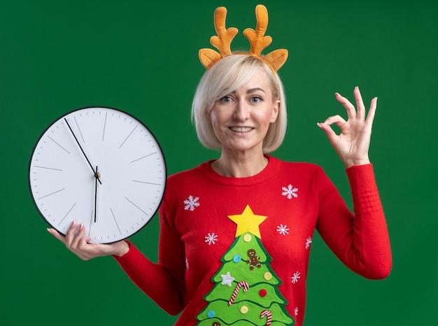 Mulher loira de meia-idade alegre usando bandana de chifres de rena de natal e suéter de natal segurando um relógio fazendo sinal de ok isolado na parede verde Foto gratuita