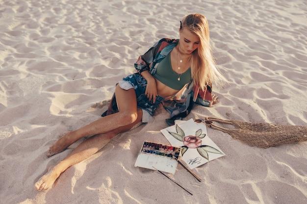 Mulher loira desenho aquarela flor por pincel na praia Foto gratuita