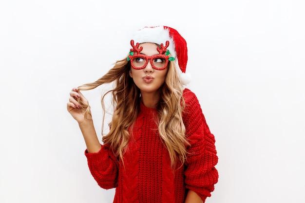 Mulher loira despreocupada e alegre em óculos de baile de máscaras fofos e chapéu de ano novo em suéter de malha vermelha, posando na parede branca. isolar. natal e o novo conceito de festa de teste. Foto gratuita