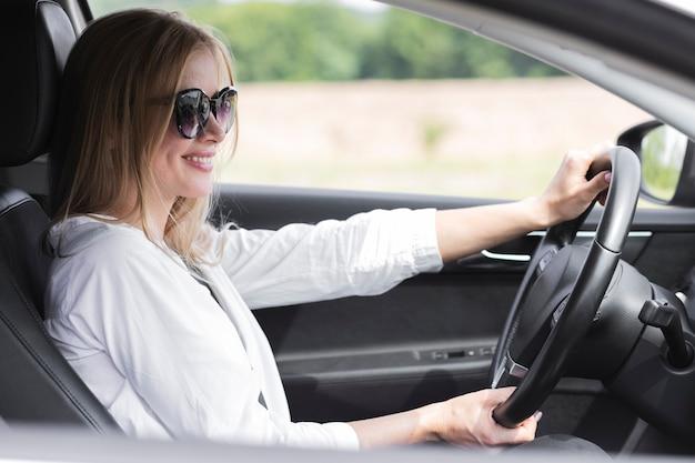 Mulher loira dirigindo um carro enquanto usava óculos Foto gratuita