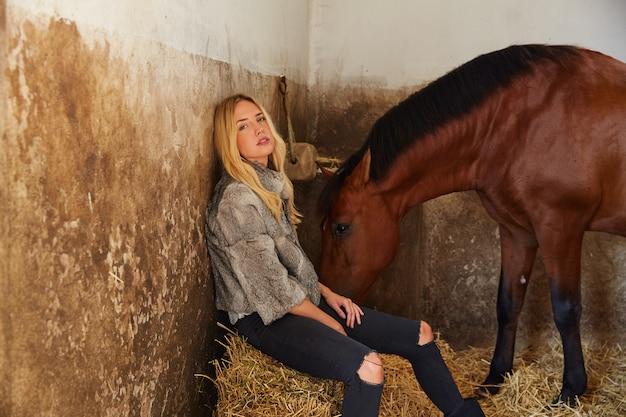 Mulher loira em um estábulo interior com cavalo Foto Premium