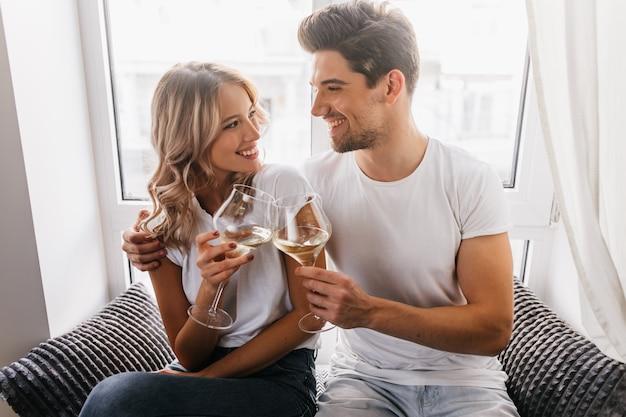 Mulher loira encaracolada olhando para o namorado enquanto bebia champanhe. casal bem-humorado comemorando feriados. Foto gratuita