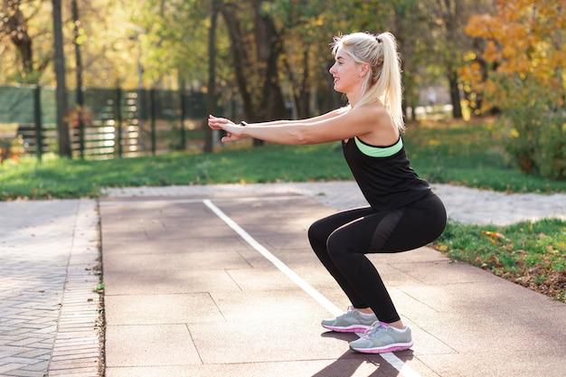 Mulher loira fazendo agachamentos fora Foto gratuita