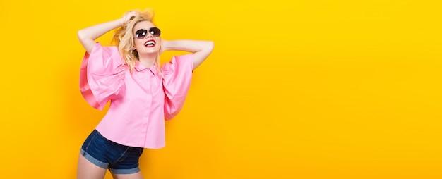 Mulher loira feliz na blusa rosa com óculos de sol Foto Premium