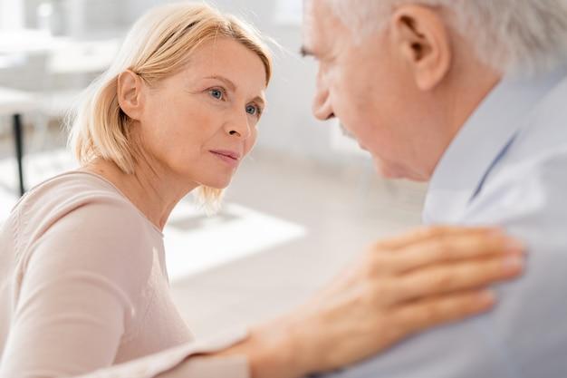 Mulher loira idosa e compassiva olhando para o homem idoso que sofre, enquanto mantém a mão em seu ombro Foto Premium