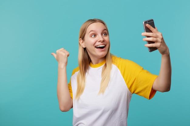 Mulher loira jovem alegre de olhos azuis e penteado casual mostrando-se animadamente à parte durante uma videochamada no smartphone, parada no azul Foto gratuita