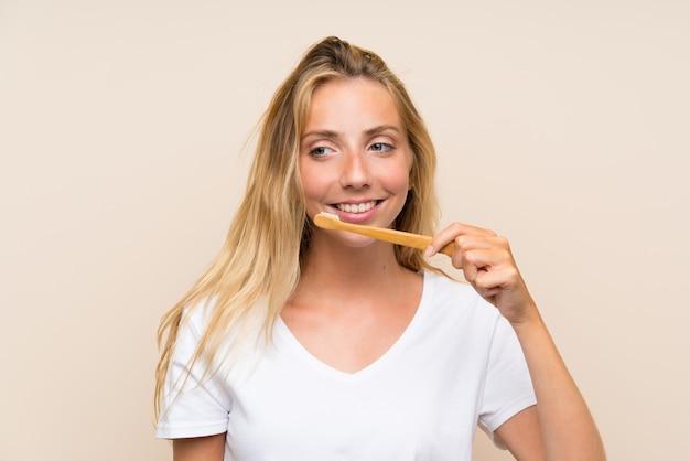 Mulher loira jovem feliz escovar os dentes Foto Premium
