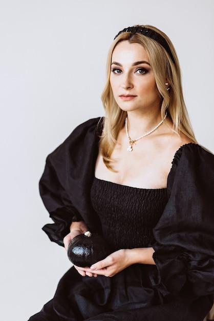 Mulher loira linda em um vestido de linho preto com uma abóbora nas mãos. moda étnica, tecido natural. festa de halloween. foco seletivo suave. Foto Premium