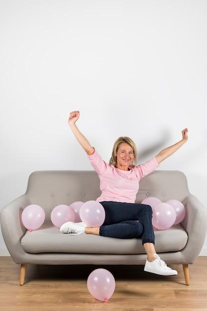 Mulher loira madura animada sentado no sofá com balões rosa, levantando os braços Foto gratuita