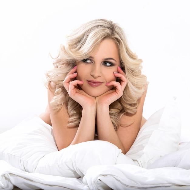 Mulher loira na cama Foto gratuita