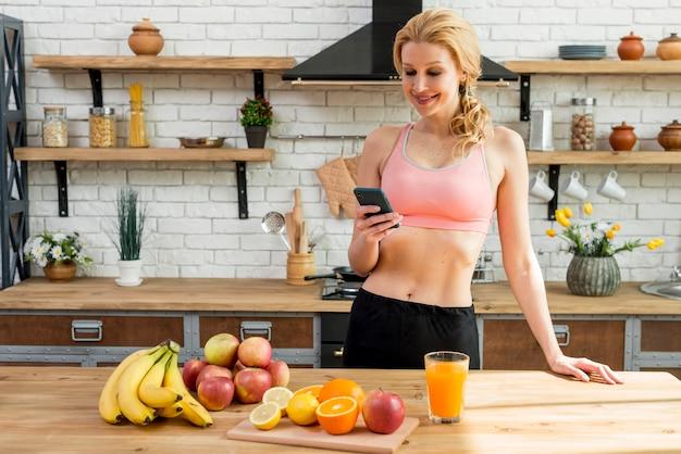 Mulher loira na cozinha com frutas Foto gratuita