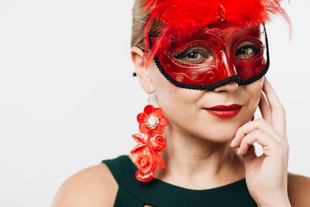 Mulher loira na máscara de carnaval vermelho Foto gratuita