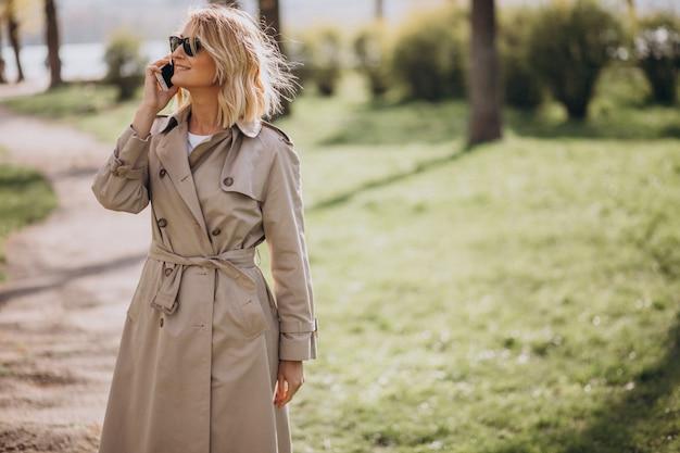 Mulher loira no casaco do lado de fora no parque usando o telefone Foto gratuita