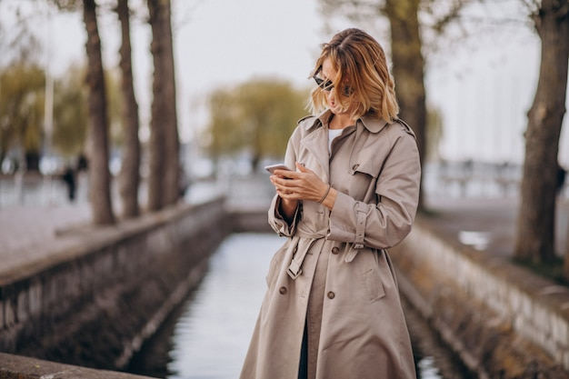 Mulher loira no casaco do lado de fora no parque Foto gratuita