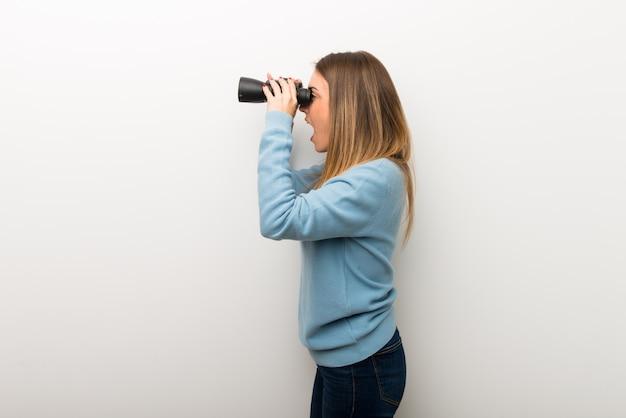 Mulher loira no fundo branco isolado e olhando à distância com binóculos Foto Premium