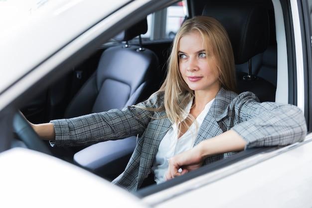 Mulher loira olhando atentamente para a estrada Foto gratuita