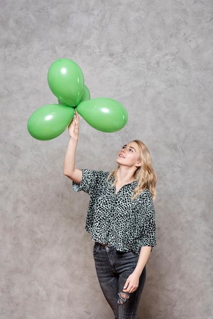 Mulher loira olhando balões verdes Foto gratuita