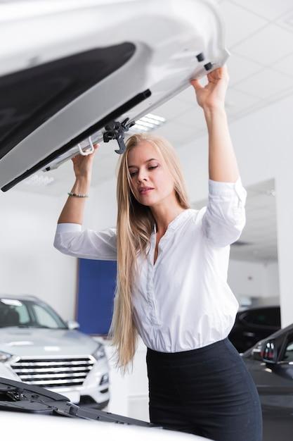 Mulher loira olhando sob o capô do carro Foto gratuita