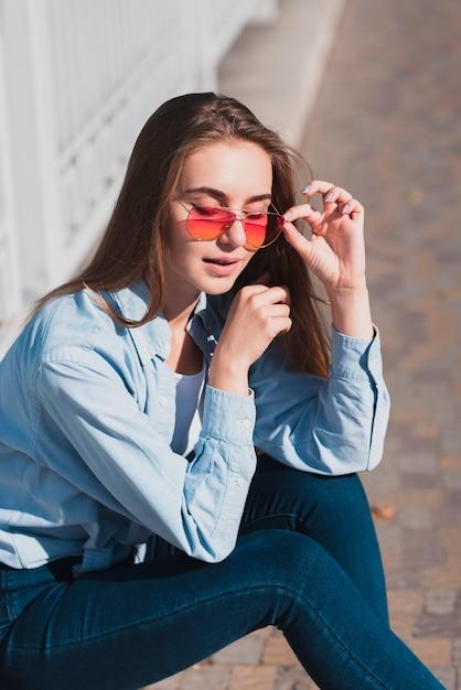 Mulher loira posando de moda com óculos de sol Foto gratuita