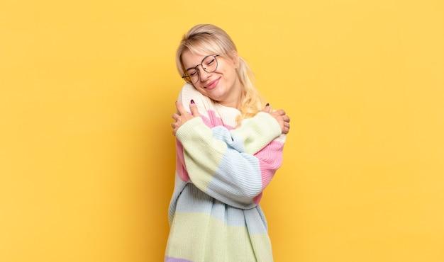 Mulher loira se apaixonando, sorrindo, se abraçando e se abraçando, permanecendo solteira, sendo egoísta e egocêntrica Foto Premium