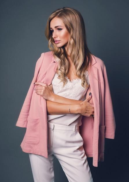 Mulher loira sedutora em jaqueta rosa posando Foto gratuita