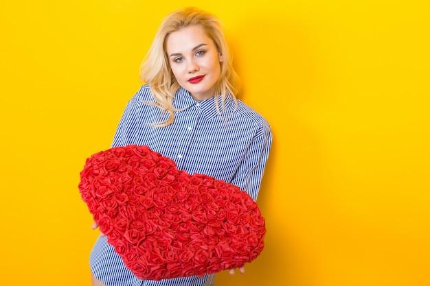 Mulher loira segurando coração grande flor vermelha. Foto Premium