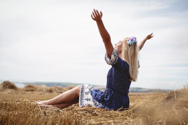 Mulher loira sentada no campo com os braços levantados Foto gratuita