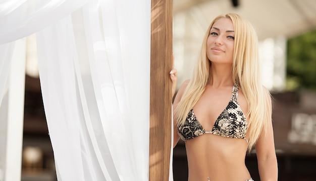 Mulher loira sexy elegante de biquíni no corpo esbelto e bem torneado bronzeado pelo sol está posando perto da piscina. Foto Premium